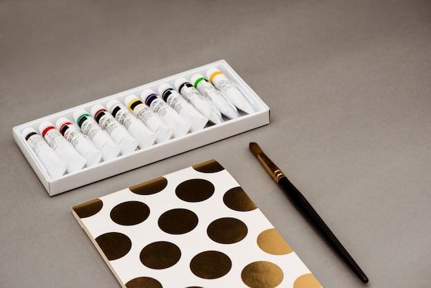 Tintas a óleo, pincel e caderno na mesa cinza