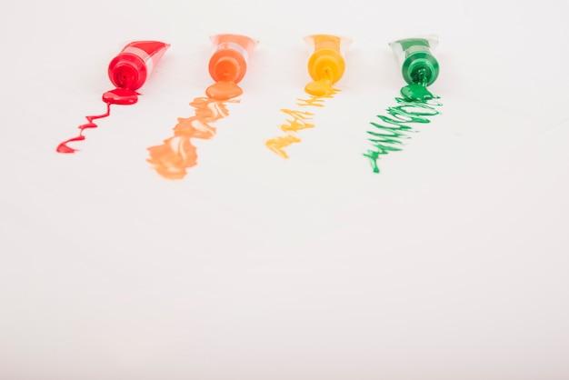 Tintas acrílicas coloridas em tubos dispostos em linha sobre fundo branco