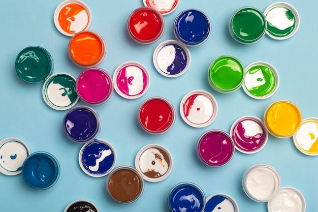 Tintas acrílicas de várias cores para desenho estão abertas sobre a mesa. fundo colorido brilhante de latas de tinta