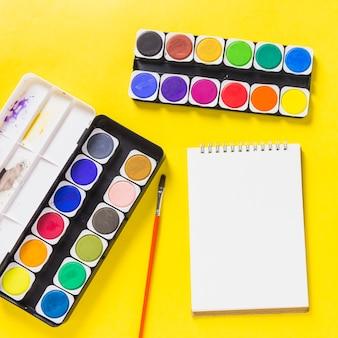 Tintas aquarela com o bloco de notas na mesa