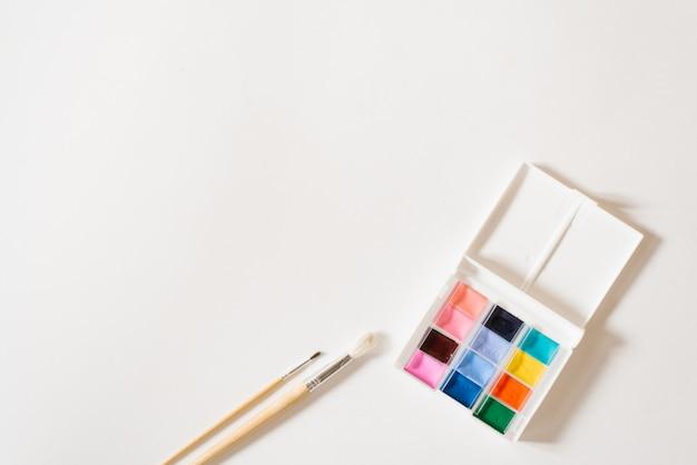 Tintas aquarela de cores diferentes nas valas em uma caixa branca e pincéis com alças de madeira sobre um fundo branco. copie o espaço. desenho e master classes para escola de arte