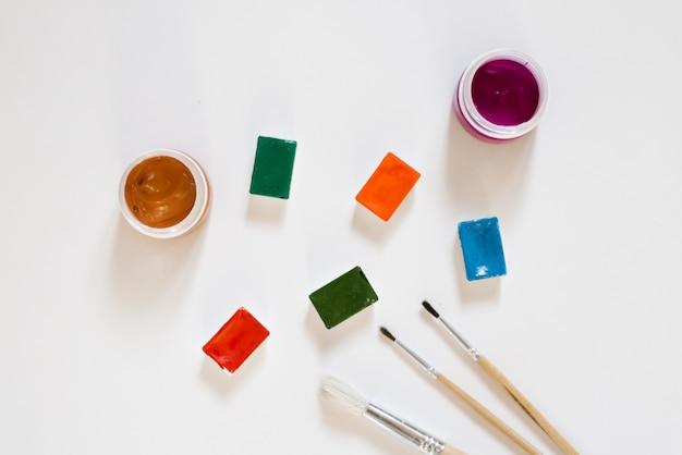 Tintas aquarela de cores diferentes nas valas em uma caixa branca e pincéis com alças de madeira sobre um fundo branco. desenho e master classes para escola de arte