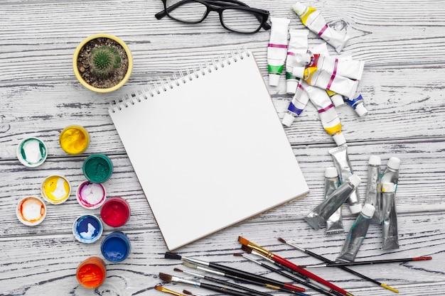 Tintas aquarela e bloco de notas em branco na mesa de madeira