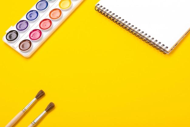 Tintas aquarela e pincéis com lona para pintura com copyspace sobre fundo amarelo