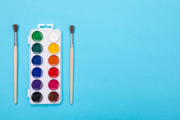 Tintas aquarela e pincéis em caixa branca, isoladas em azul