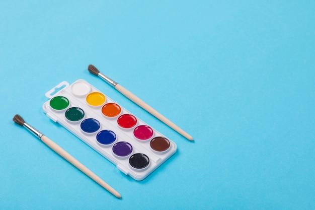 Tintas aquarela e pincéis em caixa branca, isoladas no fundo azul
