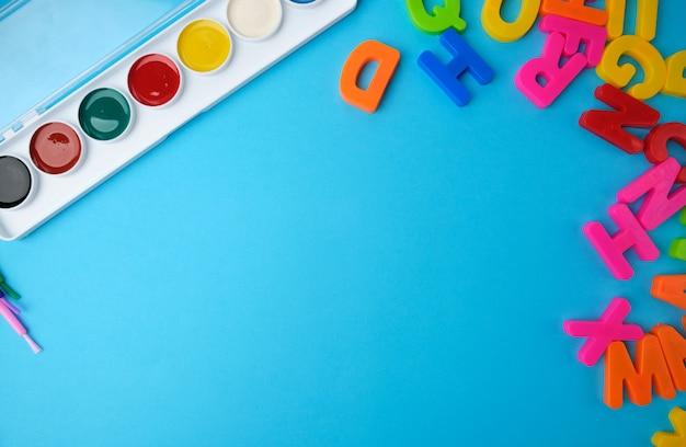 Tintas aquarela multicoloridas em uma caixa de plástico e pincéis em uma superfície azul