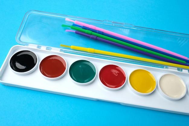 Tintas aquarela multicoloridas em uma caixa de plástico e pincéis