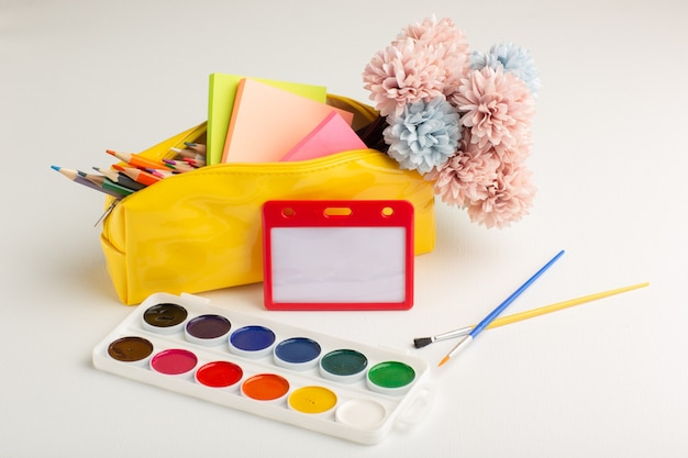 Tintas coloridas de vista frontal com borlas e flores em pintura de cor de desenho de arte de fundo branco