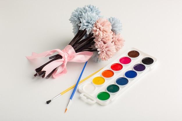 Tintas coloridas de vista frontal com flores na superfície branca