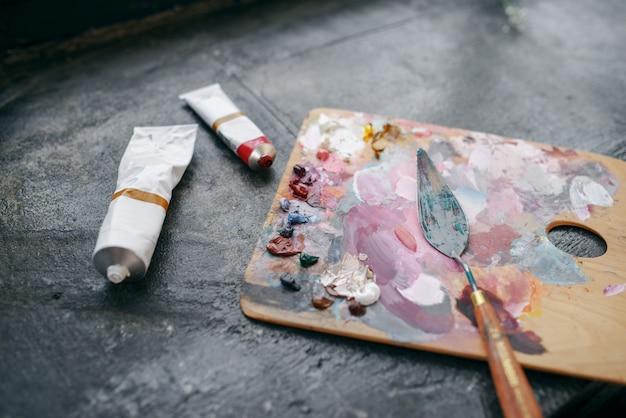 Tintas coloridas na paleta closeup, ninguém. ferramentas do pintor sobre a mesa no estúdio de arte, equipamentos no local de trabalho do artista, pincel, ateliê criativo ou oficina