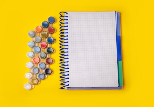 Tintas coloridas para desenho. caderno em uma mesa amarela