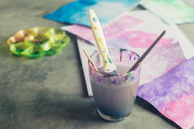 Tintas de mesa de arte em aquarela, pincéis de arte, copo de água.
