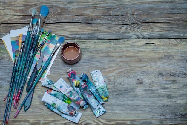 Tintas e pincéis no fundo da mesa de madeira