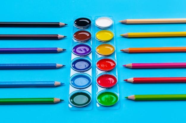 Tintas guache brilhantes para desenho localizadas no centro em um azul com lápis brilhantes ao redor dos lápis espalhados. fechar-se.