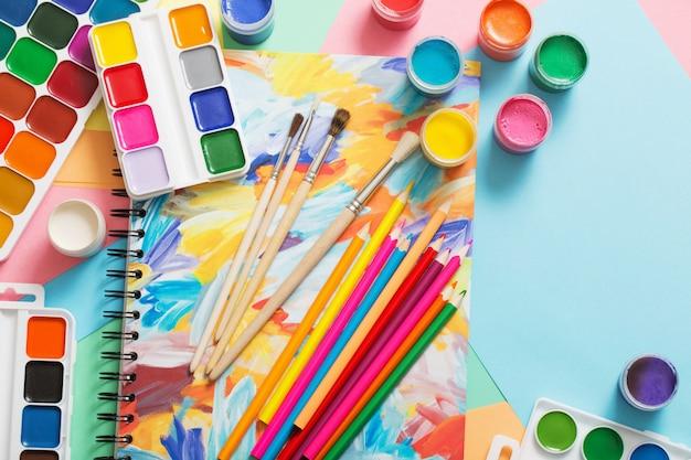 Tintas, lápis e pincéis em papel