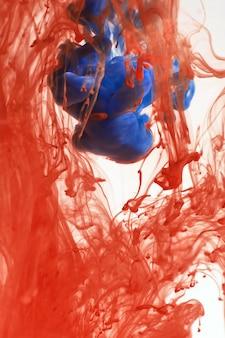 Tintas laranja e azuis se dissolvem na água, fundo branco isolado. abstração em movimento, tinta colorida circula na água