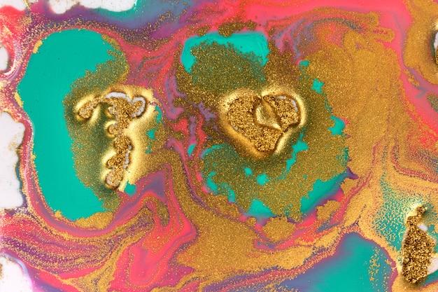 Tintas mistas rosa, douradas e azuis derramadas sobre fundo branco papel. textura de glitter dourado.