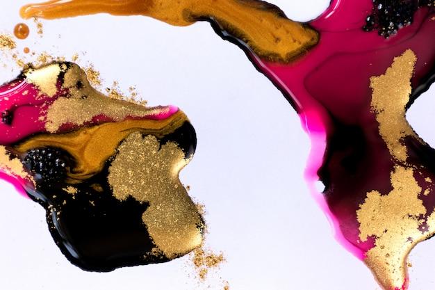 Tintas misturadas rosa, pretas e douradas sobre fundo branco papel.