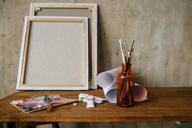 Tintas na paleta, pincel na garrafa, tela, ninguém. ferramentas do pintor na mesa do estúdio de arte, equipamentos no local de trabalho do artista, pincel
