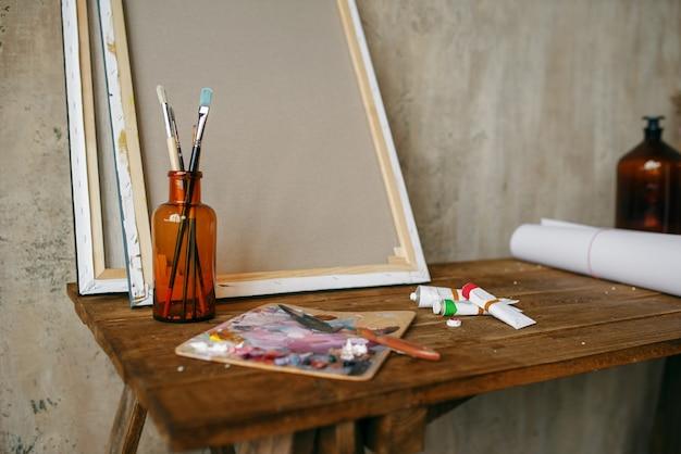Tintas na paleta, pincel na garrafa, tela, ninguém. ferramentas do pintor sobre a mesa no estúdio de arte, equipamentos no local de trabalho do artista, pincel, ateliê criativo ou oficina
