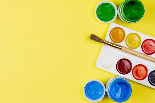 Tintas para pintar sobre fundo amarelo.