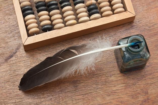 Tinteiro de vidro antigo com uma caneta de pena e ábaco em uma mesa de madeira