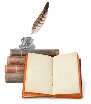 Tinteiro sobre uma pilha de livros antigos e livro aberto com páginas em branco, isoladas no fundo branco