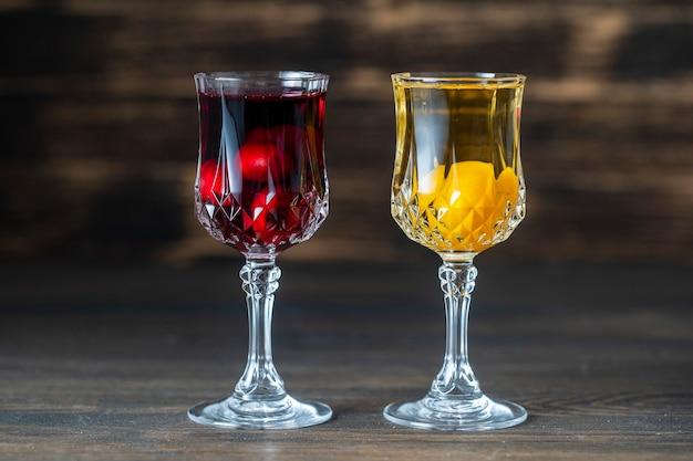 Tintura caseira de cereja vermelha e ameixa cereja amarela em taças de cristal de vinho com fundo de madeira, ucrânia, close-up. conceito de bebidas alcoólicas de frutas vermelhas