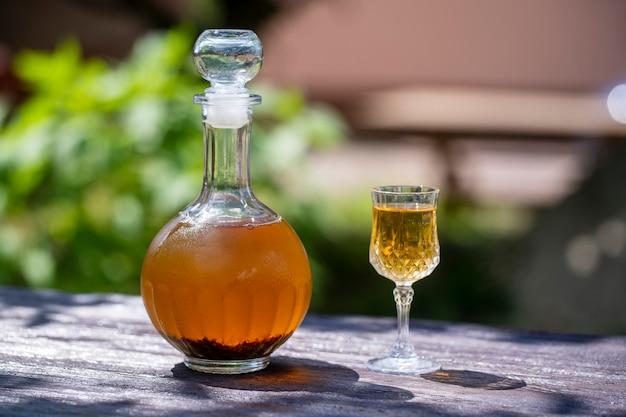 Tintura de botões de bétula caseira em uma garrafa de vidro e uma taça de cristal de vinho em uma mesa de madeira no jardim, ucrânia, close-up. conceito de bebidas alcoólicas à base de ervas