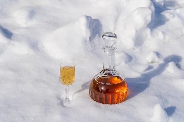 Tintura de fruta caseira em uma garrafa de vidro e uma taça de cristal de vinho em um fundo branco e de neve no inverno