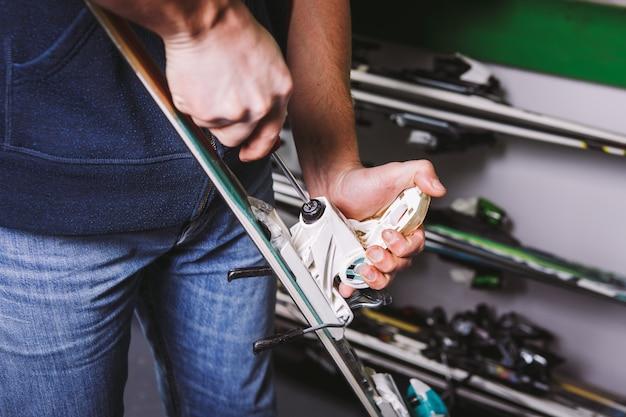 Tintura temática e reparação de equipamento de esqui. close da mão de um homem caucasiano usando uma ferramenta de chave de fenda para ajustar e torcer as amarras das botas de esqui na oficina.