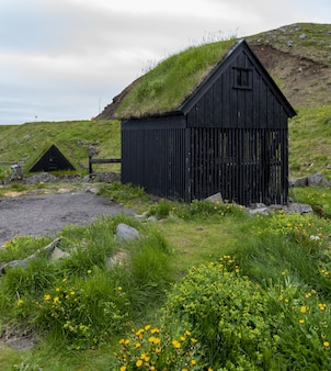 Típica vila de pescadores islandesa com casas com telhados de grama e prateleiras para secagem de peixes