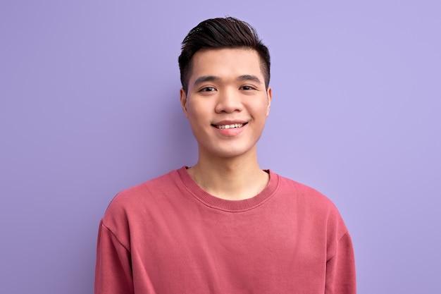 Tipo bonito cara de aparência asiática, olhando para a câmera, sorrindo, vestindo uma camisa casual.