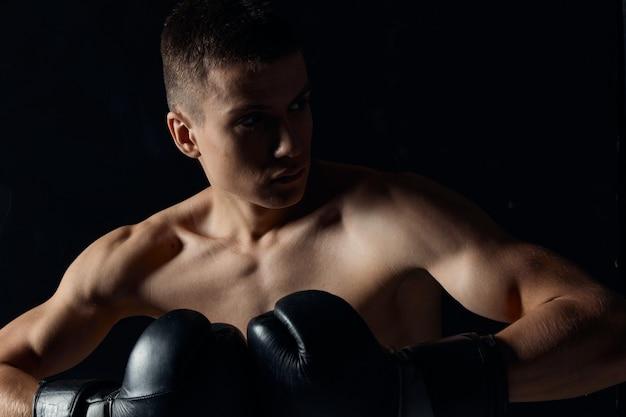 Tipo de esporte em luvas de boxe close-up retrato fundo preto vista recortada.