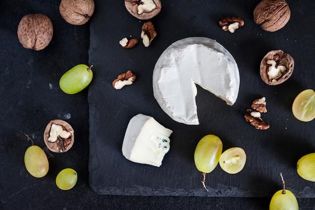 Tipo de queijo brie. queijo macio com uvas e nozes em fundo preto. camada plana, vista superior
