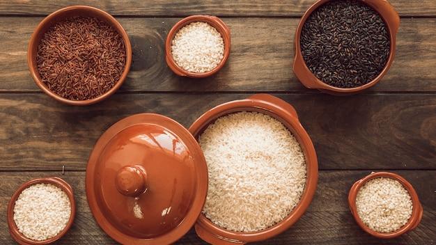 Tipo diferente cru de grãos de arroz na prancha de madeira