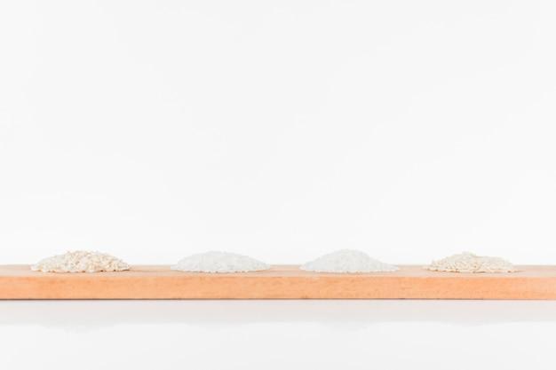 Tipo diferente de arroz na bandeja de madeira sobre o fundo branco