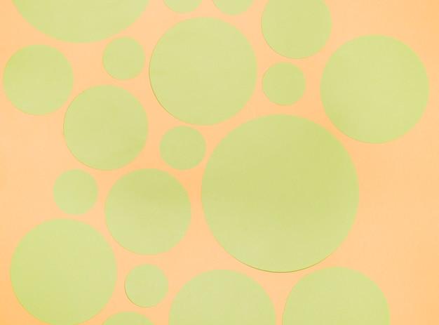 Tipo diferente de círculos de papel verde em um pano de fundo laranja