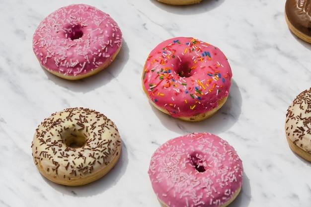 Tipo diferente de donuts no pano de fundo texturizado em mármore