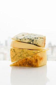 Tipo diferente de fatias de queijo triangular com ervas na mesa branca