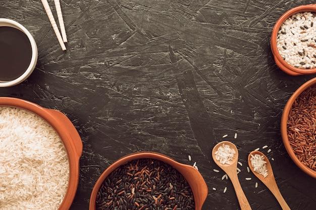 Tipo diferente de grãos de arroz tigela com molho de soja; pauzinhos e colher de pau