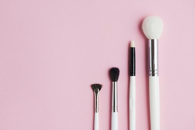 Tipo diferente de pincéis de maquiagem em uma fileira no fundo rosa