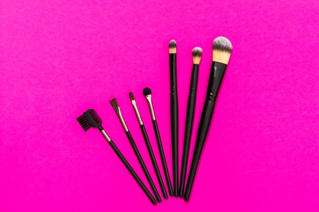 Tipo diferente de pincéis de maquiagem no fundo rosa