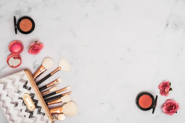Tipo diferente de pincéis de maquiagem no saco com pó facial compacto e rosa flores sobre fundo branco