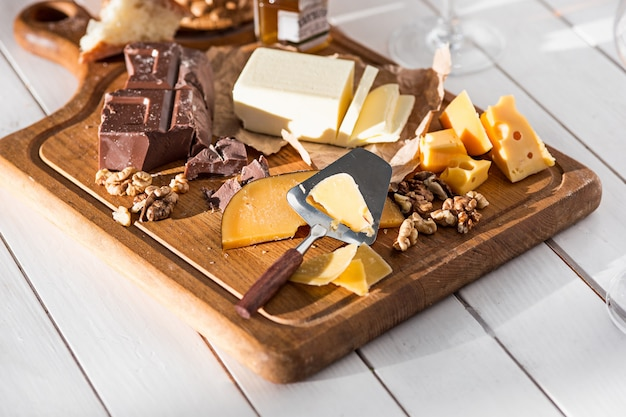 Tipo diferente de queijo e nozes na madeira