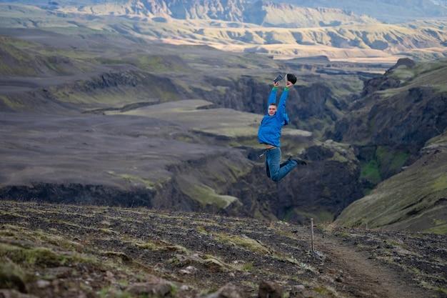 Tipo jovem caucasiano pulando sobre fundo de montanha e cânion no caminho da trilha laugavegur, islândia. promover um estilo de vida saudável.