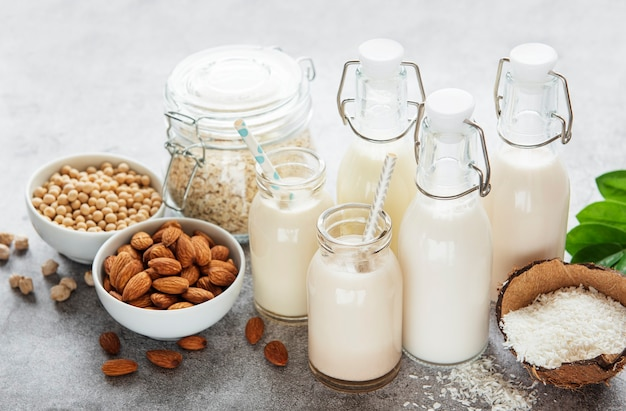 Tipos alternativos de leites veganos em garrafas de vidro em um fundo de concreto. vista do topo