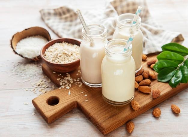 Tipos alternativos de leites veganos em garrafas de vidro em uma superfície de concreto