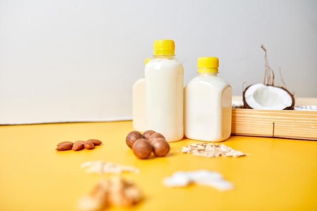 Tipos alternativos de leites veganos em garrafas em uma superfície amarela, vários ingredientes e leites vegetais veganos, leite não lácteo, leite alternativo